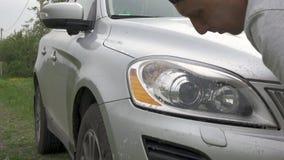 Το ενεργό άτομο στην άσπρη μπλούζα πλένει τους γκρίζους προβολείς hatchback φιλμ μικρού μήκους