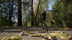 Το ενεργό κορίτσι δρομέων εφήβων που φορά τον αθλητισμό ντύνει και που χαλαρώνει μετά από το σχολείο στο πάρκο μια ημέρα φθινοπώρ φιλμ μικρού μήκους