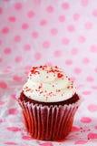 Το ενιαίο κόκκινο βελούδο cupcake με το κόκκινο ψεκάζει Στοκ φωτογραφία με δικαίωμα ελεύθερης χρήσης