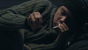 Το ενοχλημένο άστεγο άτομο αποτυγχάνει να ανάψει το τσιγάρο, εθισμός στο κάπνισμα, κινηματογράφηση σε πρώτο πλάνο φιλμ μικρού μήκους