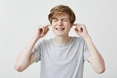 Το ενοχλημένο καυκάσιο άτομο με τη δίκαιη τρίχα σφίγγει τα δόντια που ντύνονται στην ανοικτό γκρι μπλούζα που συνδέει τα αυτιά με στοκ φωτογραφία