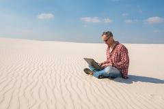 Το ενδιαφερόμενο άτομο με ένα lap-top κάθεται στην έρημο Στοκ Εικόνες