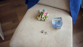 Το εξάρτημα των κομψών ατόμων για το γάμο, νερό τουαλετών με buttonhole βρίσκεται σε μια καρέκλα, το σακάκι του που κρεμά στο πίσ φιλμ μικρού μήκους