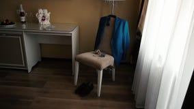 Το εξάρτημα των κομψών ατόμων για το γάμο, νερό τουαλετών με buttonhole βρίσκεται σε μια καρέκλα, το σακάκι του που κρεμά στο πίσ απόθεμα βίντεο
