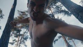 Το εξαγριωμένο επιθετικό άτομο κτυπά με τις πυγμές του το να βρεθεί πρόσωπο υπαίθριο στο δάσος φιλμ μικρού μήκους