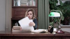 Το εξαντλημένο θηλυκό πεσμένος κοιμισμένο στο σωρό των βιβλίων στο γραφείο της και ξυπνημένος από έναν συναγερμό παίρνει γρήγορα  απόθεμα βίντεο