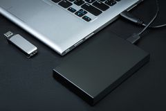 Το εξωτερικό hdd σύνδεσε με το lap-top και την κίνηση λάμψης USB σε ένα μαύρο υπόβαθρο Στοκ Φωτογραφίες