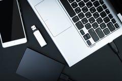 Το εξωτερικό hdd σύνδεσε με το lap-top, την κίνηση λάμψης USB και το smartphone σε ένα μαύρο υπόβαθρο Στοκ Φωτογραφία