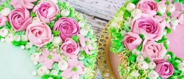 Το εορταστικό κέικ δύο με τα λουλούδια αυξήθηκε σε ένα άσπρο ξύλινο υπόβαθρο Στοκ Φωτογραφία