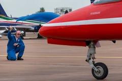 Το επίγειο μέλος του πληρώματος της Royal Air Force δίνει τις κατευθύνσεις στον πιλότο σε ένα κόκκινο βρετανικό αεροδιαστημικό γε στοκ φωτογραφία με δικαίωμα ελεύθερης χρήσης
