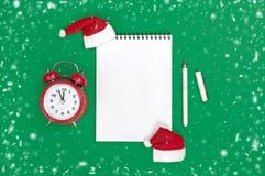 Το επίπεδο καλής χρονιάς καρτών βάζει τη σύνθεση με τον κύλινδρο και το ντεκόρ Χριστουγέννων στο πράσινο υπόβαθρο χρώματος στοκ φωτογραφία με δικαίωμα ελεύθερης χρήσης