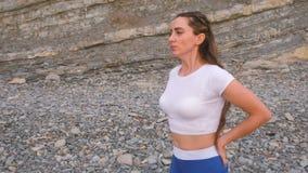 Το επίπεδο κορίτσι κοιλιών κατά τη διάρκεια της διαφραγματικής αναπνοής ασκεί bodyflex στο υπόβαθρο βράχου Πρόσωπο και άποψη κινη απόθεμα βίντεο