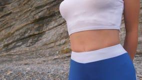 Το επίπεδο κορίτσι κοιλιών κατά τη διάρκεια της διαφραγματικής αναπνοής ασκεί bodyflex στο υπόβαθρο βράχου Άποψη κινηματογραφήσεω απόθεμα βίντεο