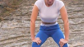 Το επίπεδο κορίτσι κοιλιών κατά τη διάρκεια της διαφραγματικής αναπνοής ασκεί bodyflex στο υπόβαθρο βράχου Άποψη κινηματογραφήσεω φιλμ μικρού μήκους