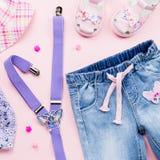 Το επίπεδο συλλογής ενδυμάτων μικρών κοριτσιών βάζει με τη floral μπλούζα, τζιν, σανδάλια στο ρόδινο υπόβαθρο στοκ φωτογραφίες με δικαίωμα ελεύθερης χρήσης