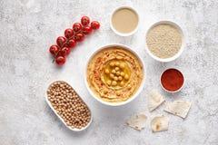 Το επίπεδο Hummus βάζει με τα ingridients, υγιή πρωτεϊνικά τρόφιμα πρόχειρων φαγητών διατροφής φυσικά χορτοφάγα Στοκ εικόνα με δικαίωμα ελεύθερης χρήσης