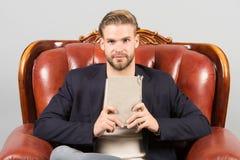 Το επίσημο κοστούμι επιχειρηματιών κάθεται στην καρέκλα δέρματος, γκρίζο υπόβαθρο Ήρεμο βιβλίο ανάγνωσης προσώπου ατόμων που μελε στοκ φωτογραφία με δικαίωμα ελεύθερης χρήσης