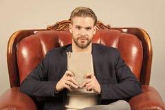 Το επίσημο κοστούμι επιχειρηματιών κάθεται στην καρέκλα δέρματος, γκρίζο υπόβαθρο Ήρεμο βιβλίο ανάγνωσης προσώπου ατόμων που μελε στοκ εικόνες