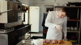 Το επαγγελματικό άτομο αρχιμαγείρων προετοιμάζει τα πλευρά κρέατος με το καρύκευμα στον τέμνοντα πίνακα στην κουζίνα εστιατορίων Στοκ Φωτογραφία