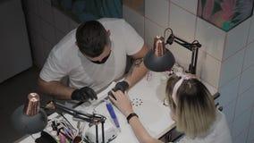 Το επαγγελματικό άτομο μανικιουριστών γυαλίζει και λειαίνει τα καρφιά του κοριτσιού με ένα αρχείο καρφιών φιλμ μικρού μήκους