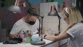 Το επαγγελματικό άτομο μανικιουριστών γυαλίζει και λειαίνει τα καρφιά του κοριτσιού με ένα αρχείο καρφιών απόθεμα βίντεο