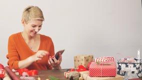 Το επαγγελματικό κορίτσι σχεδιαστών διαρκεί επάνω τις τηλεφωνικές εφαρμογές για τα αρχικά δώρα για τα Χριστούγεννα απόθεμα βίντεο