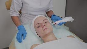 Το επαγγελματικό cosmetologist εκτελεί τη διαδικασία DermaPen σε μια cosmetology κλινική φιλμ μικρού μήκους