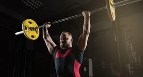 Το επαγγελματικό powerlifter ανυψώνει το φραγμό επάνω από το κεφάλι του σε μια στάση οκλαδόν Στοκ Εικόνα