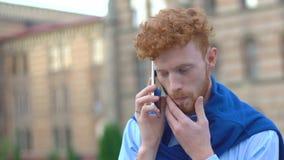 Το επικεφαλής άτομο πιπεροριζών Throughtful με τη γενειάδα μιλά μέσω του κινητού τηλεφώνου στο θολωμένο υπόβαθρο του κτηρίου κλεί απόθεμα βίντεο