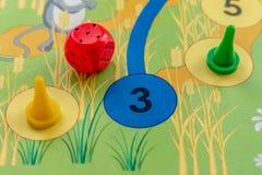 Το επιτραπέζιο παιχνίδι παιδιών ` s με τα τσιπ και χωρίζει σε τετράγωνα τη ρίψη στοκ φωτογραφίες