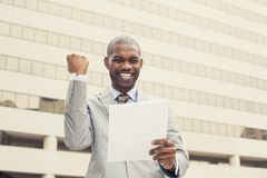 Το επιτυχές άτομο γιορτάζει την επιτυχία που κρατά τα νέα έγγραφα συμβάσεων Στοκ Φωτογραφίες