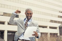 Το επιτυχές άτομο γιορτάζει την επιτυχία που κρατά τα νέα έγγραφα συμβάσεων Στοκ Εικόνες