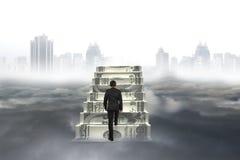 Το επιχειρησιακό άτομο αναρριχείται στα σκαλοπάτια χρημάτων με το τοπίο πόλεων cloudscap Στοκ Φωτογραφίες