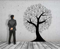 Το επιχειρησιακό άτομο βλέπει την εικόνα έννοιας του δέντρου ιδέας στο άσπρους πάτωμα και το συμπαγή τοίχο τούβλου Στοκ εικόνα με δικαίωμα ελεύθερης χρήσης