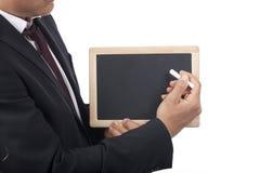 Το επιχειρησιακό άτομο γράφει με την κιμωλία στο μαύρο πίνακα στοκ εικόνες με δικαίωμα ελεύθερης χρήσης