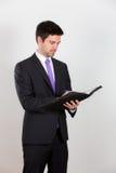 Το επιχειρησιακό άτομο γράφει σε ένα σημειωματάριο στοκ φωτογραφία με δικαίωμα ελεύθερης χρήσης