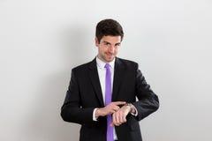 Το επιχειρησιακό άτομο δείχνει στο ρολόι και το χαμόγελό του στοκ εικόνες