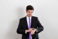 Το επιχειρησιακό άτομο δείχνει στο ρολόι και το χαμόγελό του στοκ εικόνα με δικαίωμα ελεύθερης χρήσης