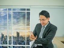 Το επιχειρησιακό άτομο ελέγχει το κινητό τηλέφωνό του στοκ εικόνα