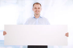το επιχειρησιακό άτομο εμβλημάτων παρουσιάζει το λευκό χαμόγελου Στοκ φωτογραφία με δικαίωμα ελεύθερης χρήσης