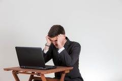 Το επιχειρησιακό άτομο κάθεται απελπισμένο σε ένα lap-top στοκ φωτογραφίες με δικαίωμα ελεύθερης χρήσης