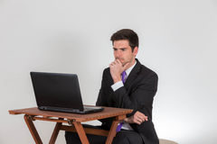 Το επιχειρησιακό άτομο κάθεται σκεπτικά σε ένα lap-top στοκ εικόνα με δικαίωμα ελεύθερης χρήσης