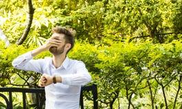 Το επιχειρησιακό άτομο κάθεται ing τον κήπο και λυπημένος Στοκ Εικόνα