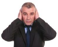 Το επιχειρησιακό άτομο καλύπτει τα αυτιά του Στοκ Φωτογραφίες