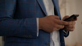 Το επιχειρησιακό άτομο κρατά το τηλέφωνο στεμένος στο εσωτερικό φιλμ μικρού μήκους