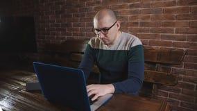 Το επιχειρησιακό άτομο με τα γυαλιά στο γραφείο ανοίγει το lap-top και αρχίζει στο πληκτρολόγιο φιλμ μικρού μήκους