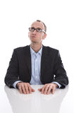 Το επιχειρησιακό άτομο με τα γυαλιά στο γραφείο σκέφτεται για κάτι - Στοκ Εικόνες