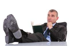 Το επιχειρησιακό άτομο με το βιβλίο κάθεται με τα πόδια στο γραφείο Στοκ Φωτογραφία