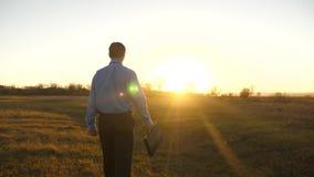 Το επιχειρησιακό άτομο με το χαρτοφύλακα πηγαίνει στο όμορφο ηλιοβασίλεμα μετά από την εργάσιμη ημέρα φιλμ μικρού μήκους