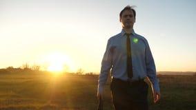 Το επιχειρησιακό άτομο με το χαρτοφύλακα στο χέρι του και στο μπλε πουκάμισο με το δεσμό μπαίνει στο ηλιοβασίλεμα μέσα το έντονο  απόθεμα βίντεο